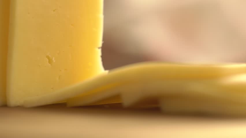 Slicing cheese into pieces closeup, super slow motion. Closeup shot of a piece of cheese. Somebody is cutting cheese with a knife.