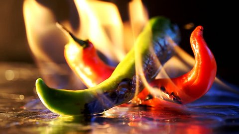 hot pepper in fire arms  /  hot pepper in flames on a black background