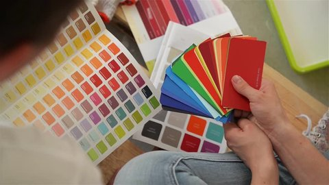 Young couple selecting a color for a condo. Young family chooses a color for repairs in a new apartment, close-up