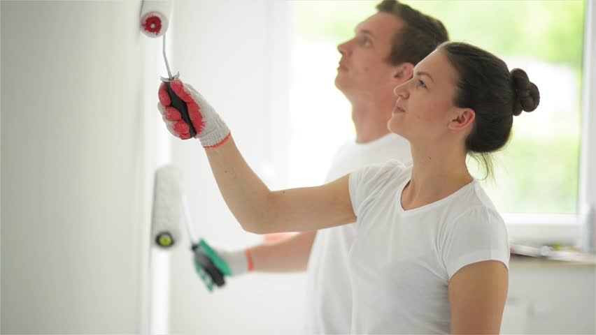 Young couple decorate their new apartment. Young husband and wife are painting the wall. Beautiful couple making repairs in their new flat.   Shutterstock HD Video #16801303