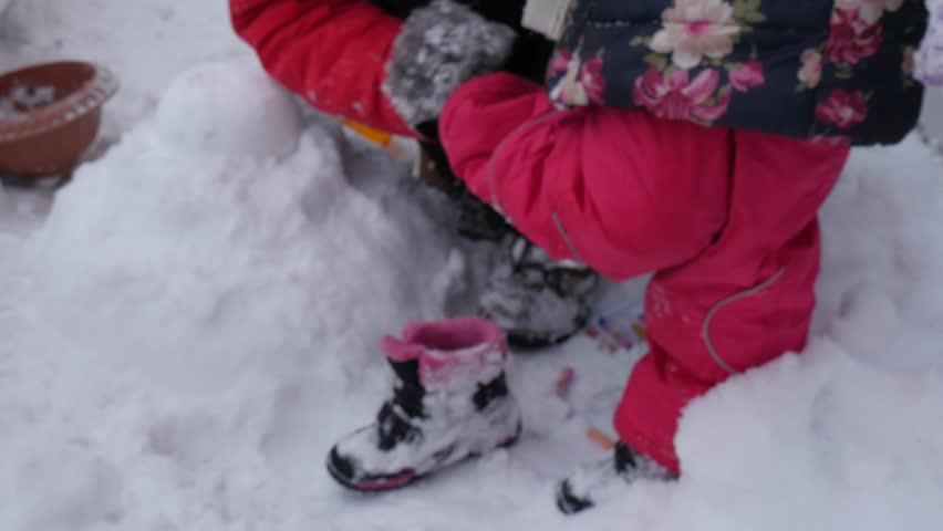 Dad is Putting Boots on the Daughter's Leg. Dad and Daughter Are Playing With Snow Together, Snowman is Made of Snow, Spending the Time Together, Have a Rest Together, Man in Red Sporty Jacket  | Shutterstock HD Video #16832701