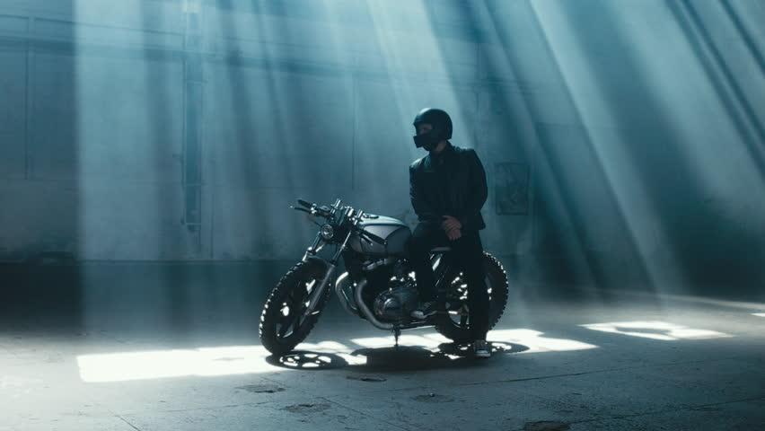 4K cinemagraph - young Caucasian male biker in leather jacket sitting on his custom cafe racer motorcycle in large warehouse garage looking forward. Background fog seamless loop