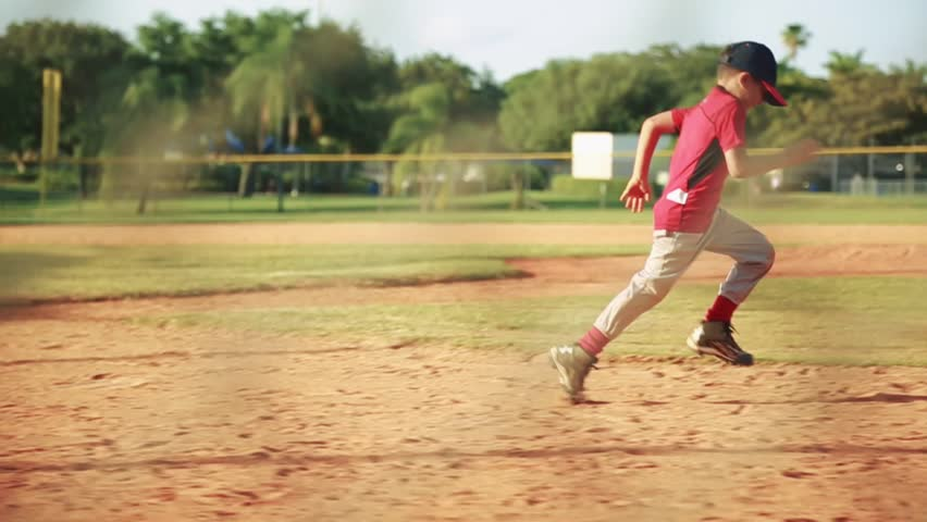Slow motion of kid running to first base during baseball practice