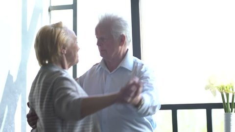 Active retirement and leisure activities, happy dance of an elderly couple. Husband kisses wife