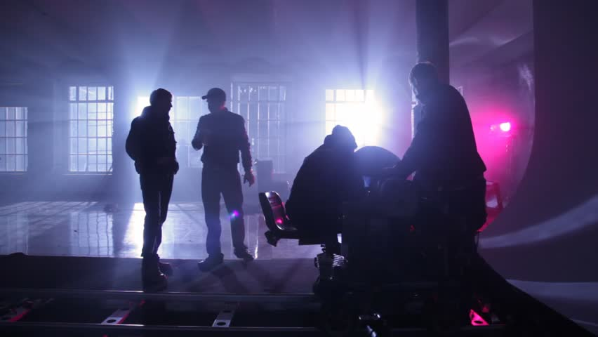 film crew adjusts equipment on rail cart in dark room shined artificial light behind windows