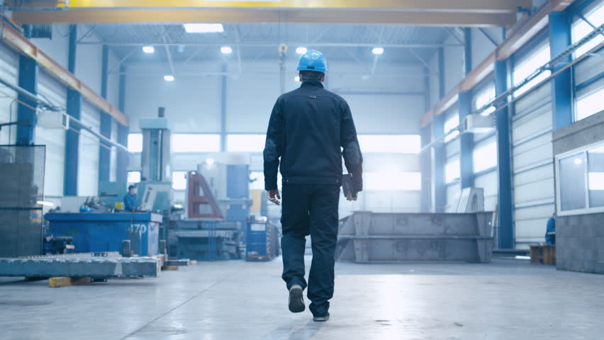 Follow footage of factory worker in a hard hat that is walking through industrial facilities. Shot on RED Cinema Camera.