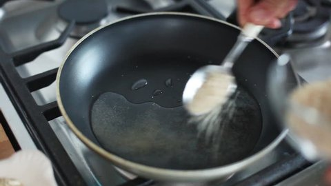 Barcelona, Spain - November 11, 2012: Woman putting water and sugar in frying pan on stovetop
