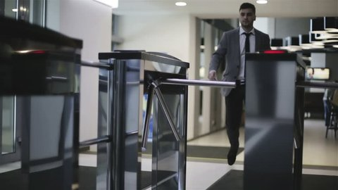 The businessman is passing through a turnstile. A man in a jacket and white shirt opens turnstile via card and comes into a business center.