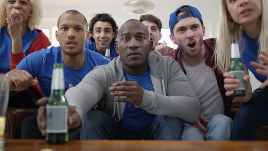 4K Friends watching sports game on TV have negative reaction to action on screen UK - April, 2016