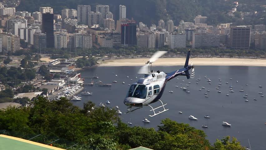 RIO DE JANEIRO, BRAZIL - CIRCA JUNE 2011: A military helicopter hovers with hills in the background, then descends onto rooftop landing spot circa June 2011 in Rio de Janeiro.