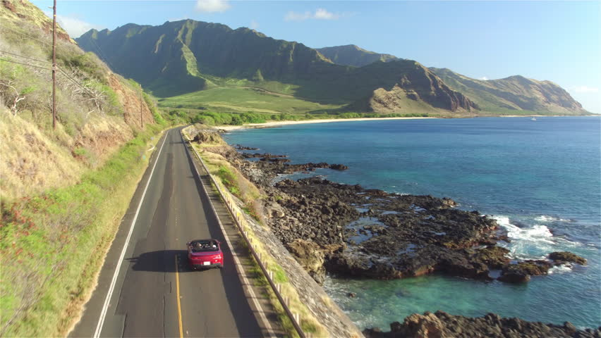 AERIAL: Red convertible car driving along the coastal road above dramatic rocky shore towards volcanic mountains. Happy young couple on summer vacation traveling at the seaside in Oahu island, Hawaii #17029471