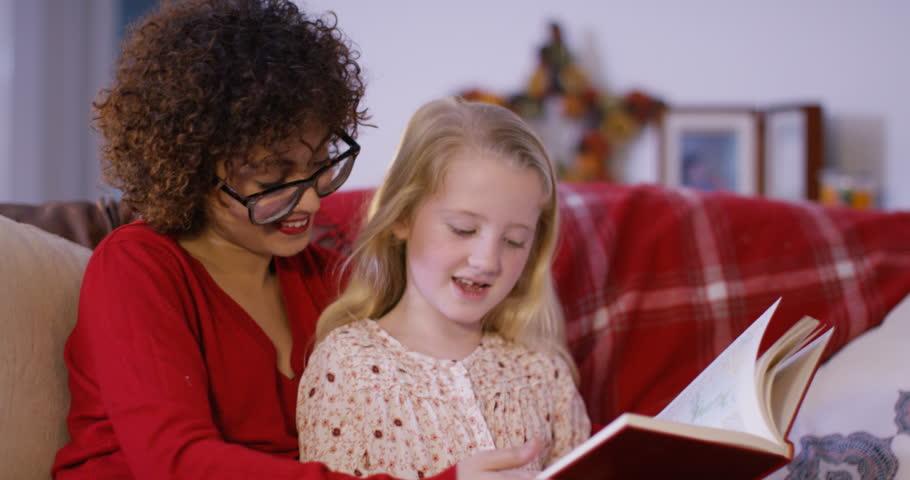 4K Babysitter & little girl reading together at home. Shot on RED Epic. UK - April, 2016