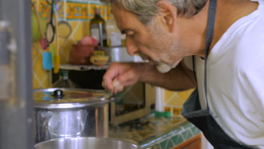 A man in his 60s tastes soup out of a large pot and adds salt without measuring the amount.