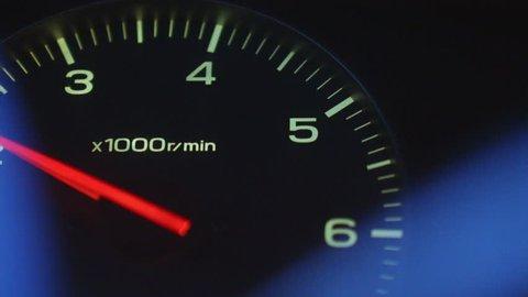 The car picks up speed, tachometer