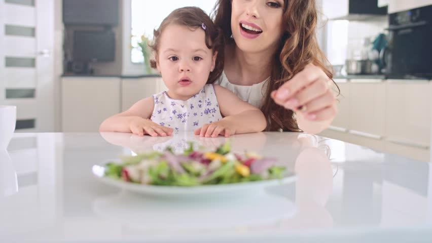 Mother feeding her little daughter , slow motion handheld type shot