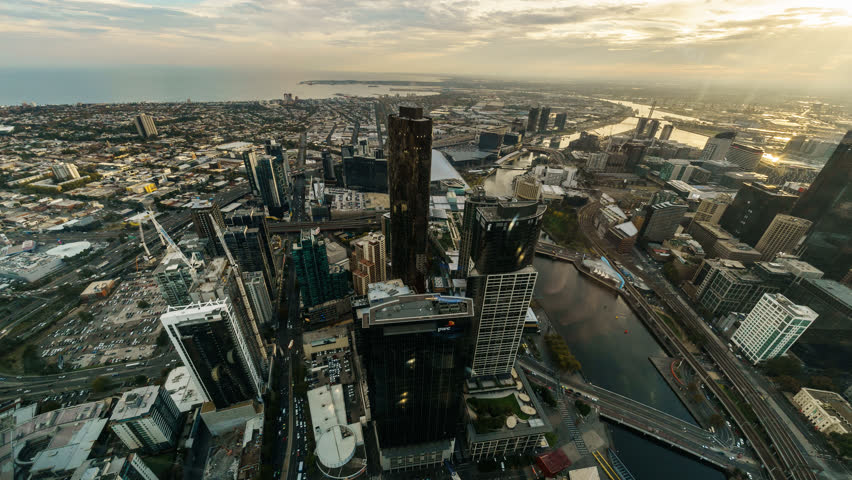 Aerial view of Melbourne cityscape including Yarra River and Victoria Harbour in the distance. Time lapse with stacked images creating artististic short brush stroke effect on the clouds. #17105311