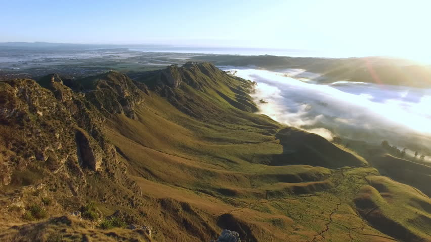 An early morning aerial tracking shot along a rocky, steep outcrop above a fog filled river valley and the sea in the distance
