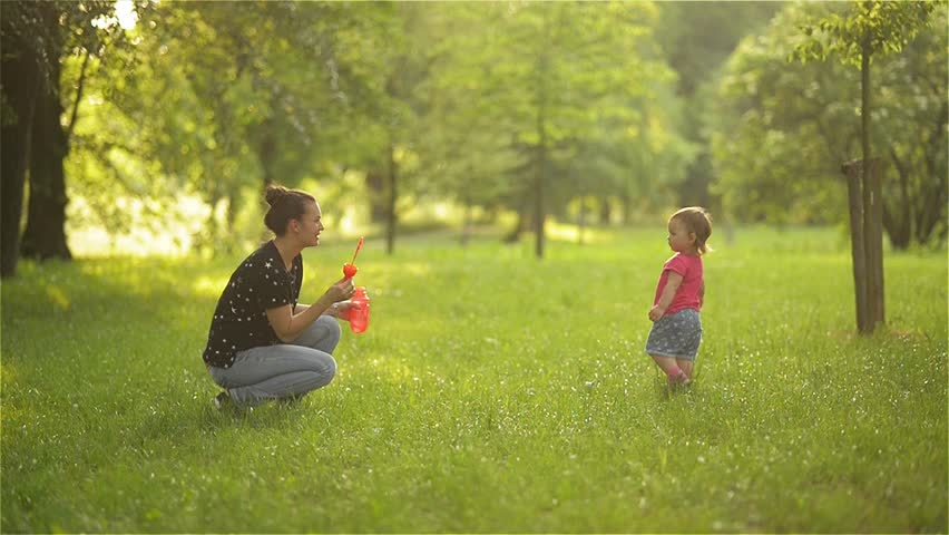 Mother and little girl daughter child blowing soap bubbles outdoor. Parent and kid having fun in park.