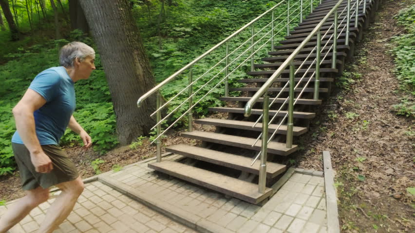 Adult man running jogging up the stairs outdoors in a forest nature on a forest trail