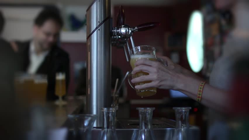 Female Bartender Serving Pints Of Beer To Crowd In The Bar. Female Bartender pouring a perfect draft beer and serving the crowd in the bar