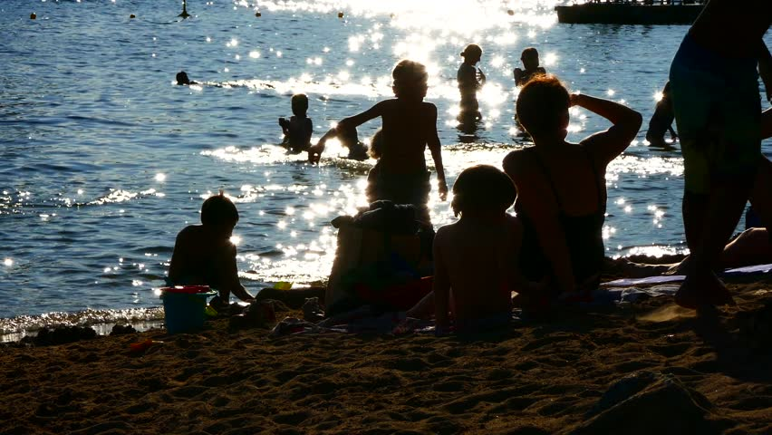 STOCKHOLM, SWEDEN, JUNE 2016: Crowd of silhouette unrecognized people enjoying water and the beach - playing together splashing water  | Shutterstock HD Video #17213851