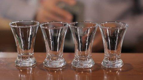 Bartender pours four shots of alcohol. Close up