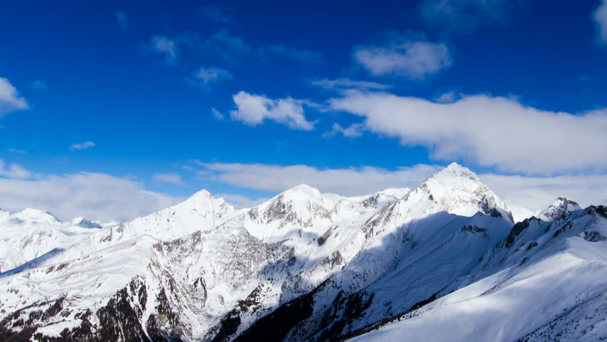 Beautiful alpine weather time lapse shot paning along the towering peaks of the Hohe Tauern mountain range in Tirol, Austria, during a sunny winter day.  | Shutterstock HD Video #17239801