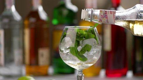 Bottle pours drink into glass. Mint leaves inside a wineglass. Sweet elderflower syrup. Key ingredient for hugo cocktail.