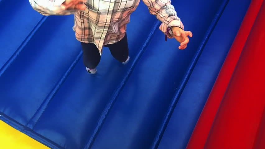 Young girl (age 6) jumps on bouncing castle and scream up to the camera.