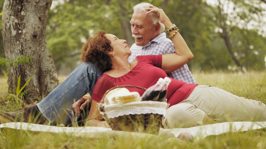 Old people, senior couple, elderly man and woman, husband and wife in park, happy retired seniors, retirement age and love. Outdoors activities, fun. Grandpa and grandma at picnic. Slow motion
