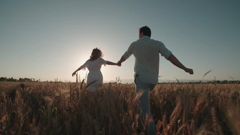 Happy, young couple running across the wheat field,sunset light, summer season.High speed camera,slow motion