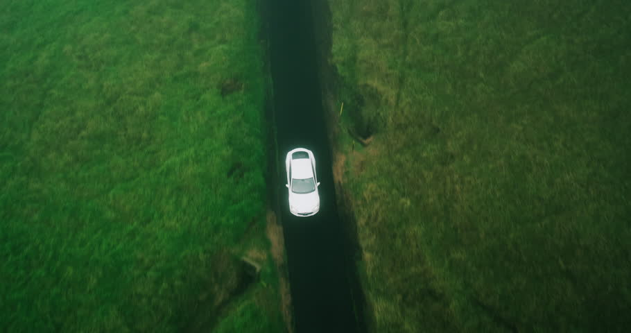 Aerial view electric car driving on country road, luxury car driving through mist at dusk with headlights | Shutterstock HD Video #17354416