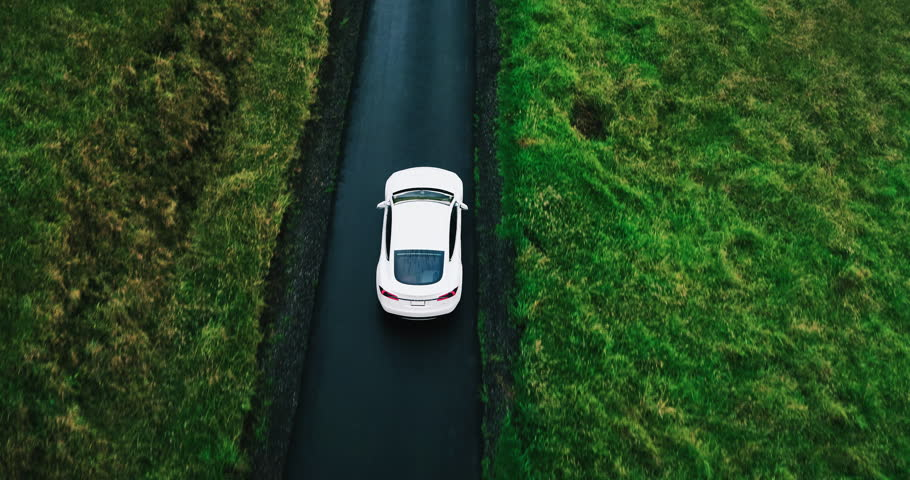 Aerial view electric car driving on country road, luxury car driving through mist at dusk with headlights #17354431