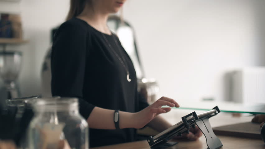 Female barista using touchscreen to make cash operation
