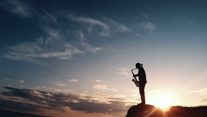 Man playing the saxophone at sunset