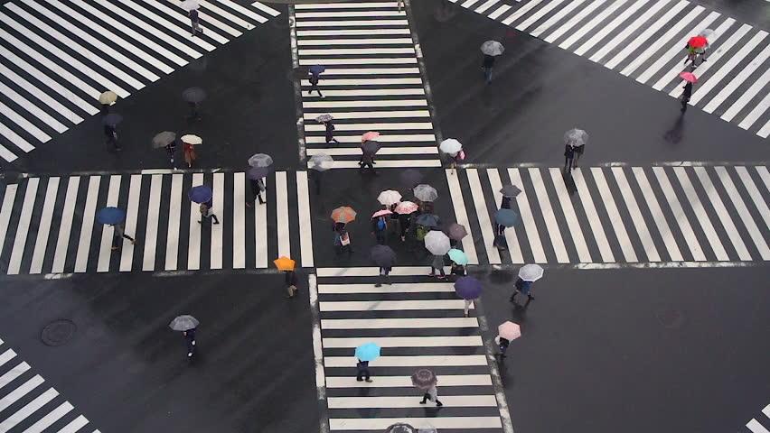 TOKYO, JAPAN - JANUARY 2016: View over Ginza crossing in the rain with umbrellas, Sukiyabashi, Tokyo, Japan