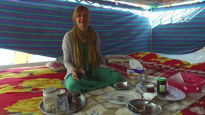 Happy blonde woman drinking coffee on felucca boat