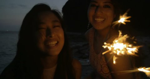 Fun International girls on the beach playing with fire work sparklers 4K.