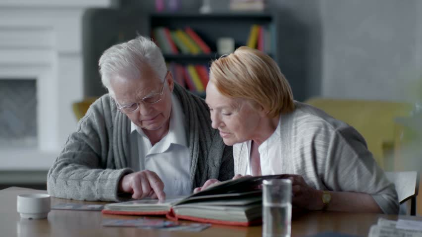 elderly happy couple spend time together and nostalgic. they looking old photo album and smiling