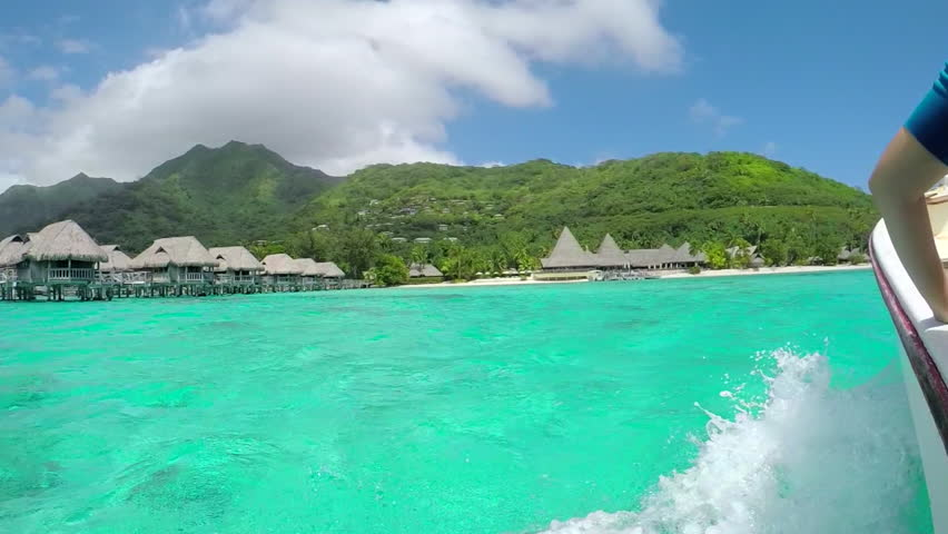 SLOW MOTION: Sailing in crystal clear ocean waters of French Polynesia past luxurious wooden over-water villas in Moorea island towards beautiful white sand beach seashore. | Shutterstock HD Video #17495101