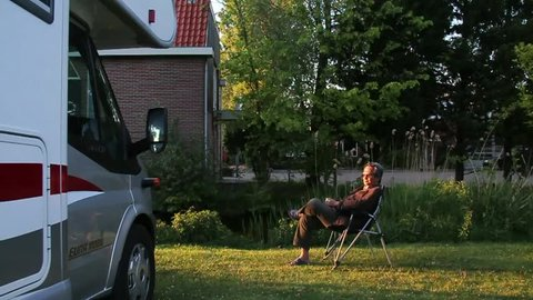 AMSTERDAM, THE NETHERLANDS - 30 APRIL 2014 : Senior man relax on portable chair in a camping ground during early morning beside a motor home.