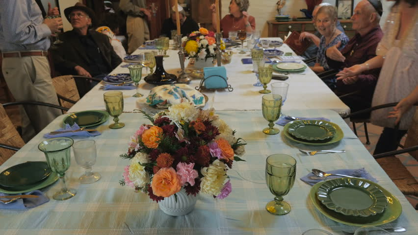 Pan up of a large table as guests arrive to a passover seder including men wearing yarmulkes.