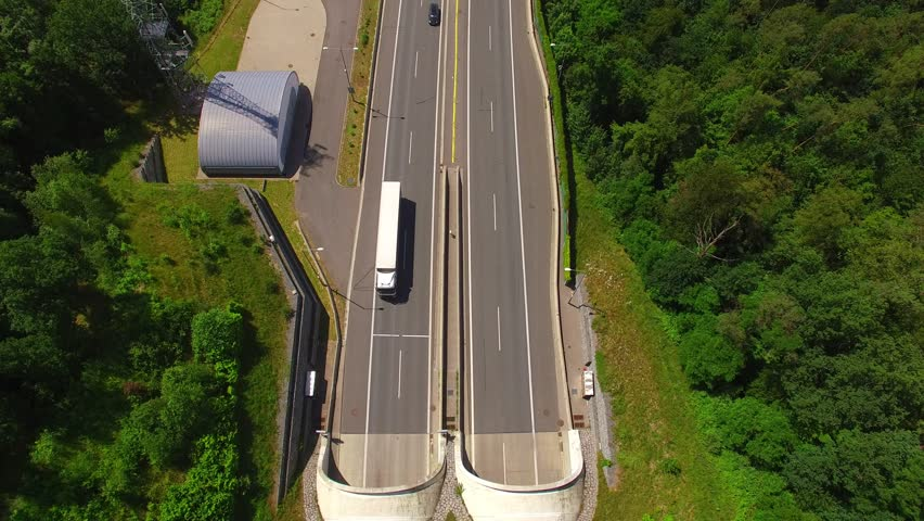 Camera flight over highway tunnel in mountains. Traffic on the road. Transportation from above. Industrial background. | Shutterstock HD Video #17532418