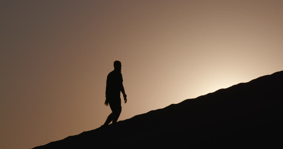 4K view of male tourist in silhouette walking up a sand dune with the rising sun in the background inside the Namib-Naukluft National Park | Shutterstock HD Video #17540866