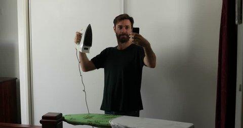 man ironing taking selfies with iron