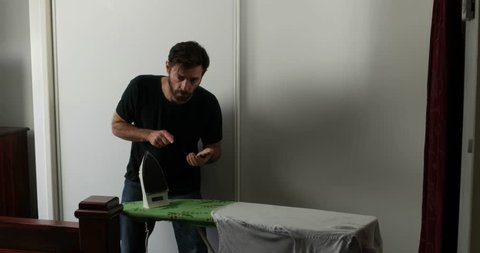 man ironing using smartphone for instructions