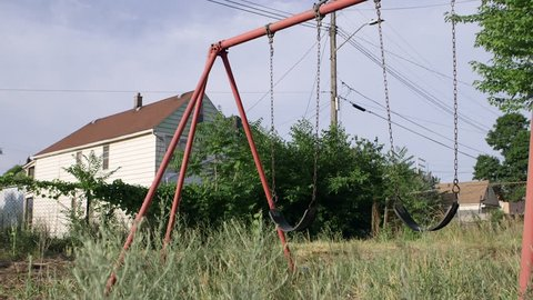 Swings blow in the breeze on Detroit abandoned playground. Blight has become a huge problem for Detroit neighborhoods, leaving playgrounds empty and grass long and uncut. urban decay, ghetto, blight
