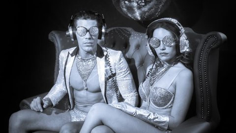 Two silver sexy disco characters. a male and female in sparkling silver costumes, great for fashion, style and events