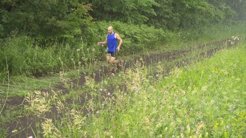 Slow motion. Male runner exercising and training outdoors in nature. traill-running.Rainy day