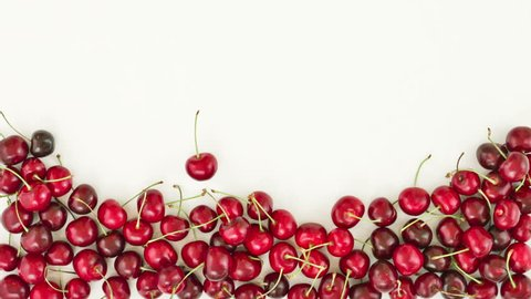 Falling down of fresh cherries on white background. Top view. stop motion animation, 4K